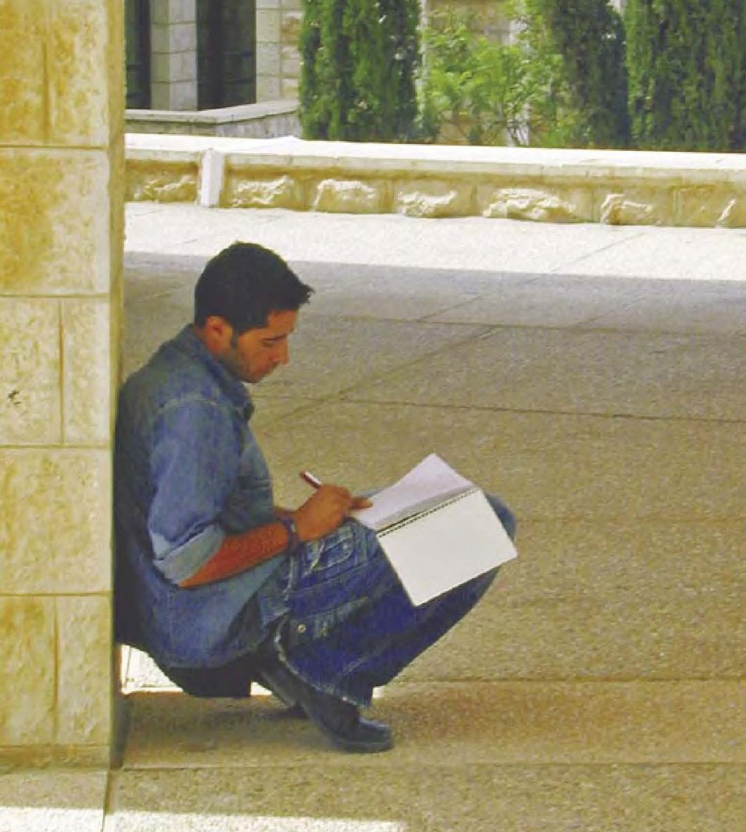 Palestinian student writing in notebook