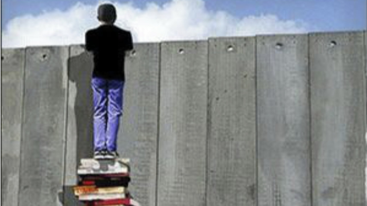 Palestinian student stands on pile of books and looks over Separation Wall