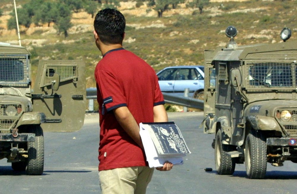 Palestinian student faces Israeli jeeps