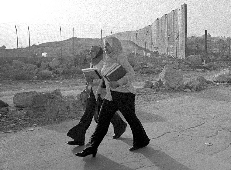Palestinian students stride past Separation Wall