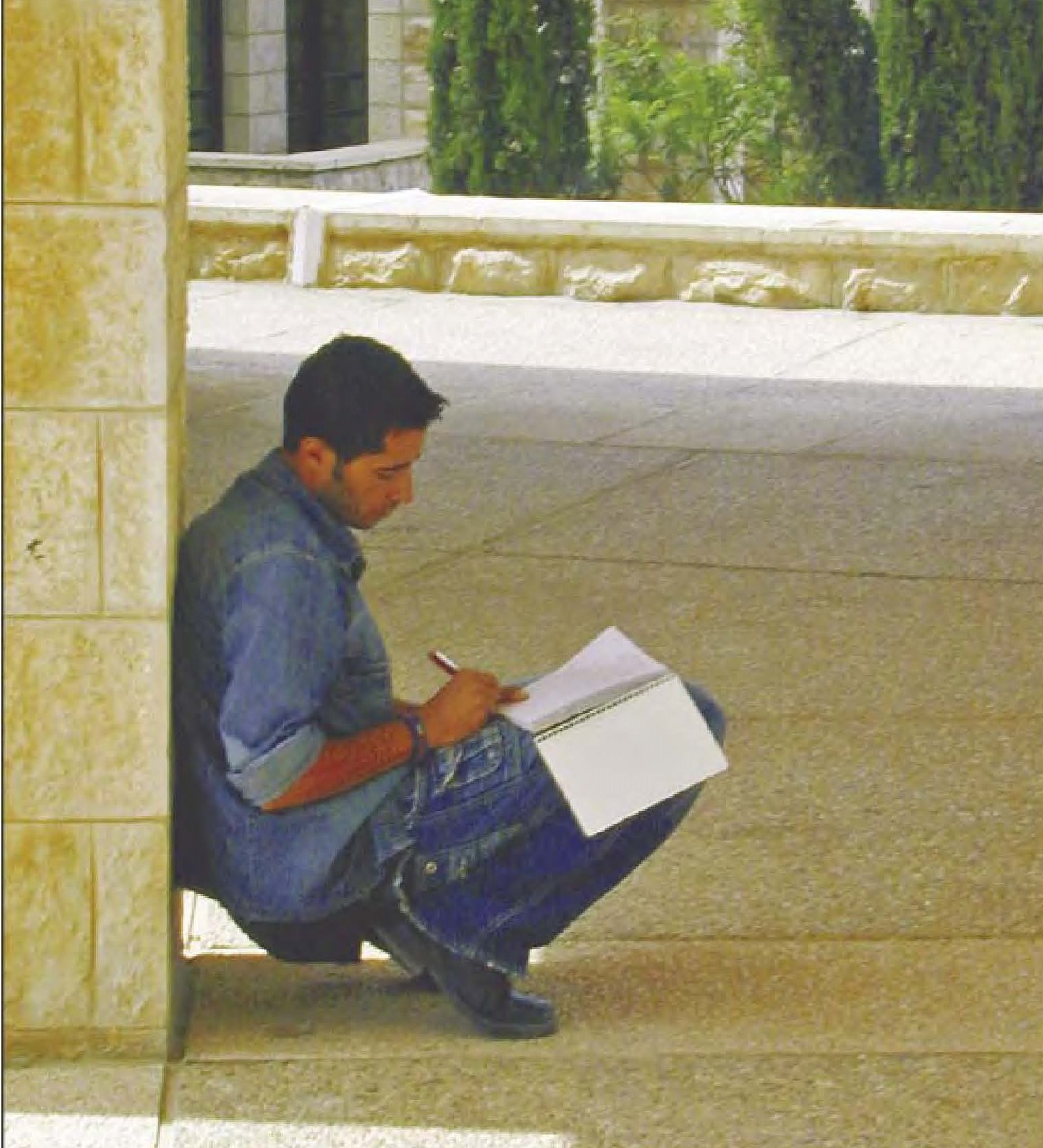 Palestinian student working in notebook