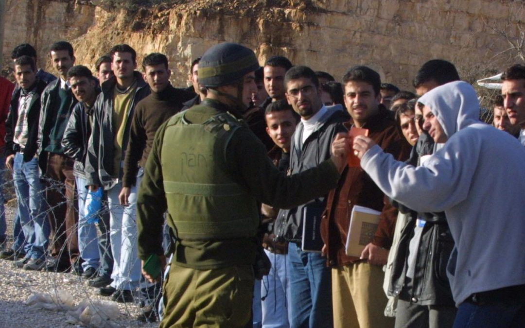 Palestinian students remonstrate with Israeli soldier at checkpoint