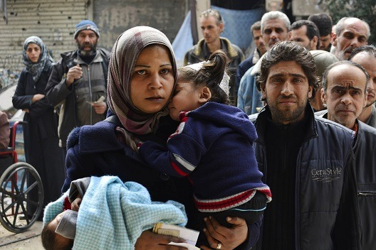 Palestinian refugees queue to receive humanitarian aid in Syria