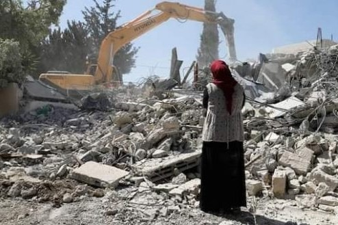 Woman looks at the ruins of her house demolished by Israeli forces 2020